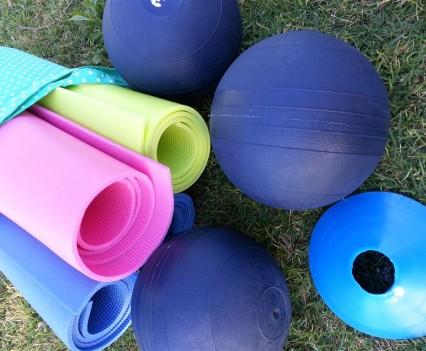 Yoga mats and medicine balls on the grass