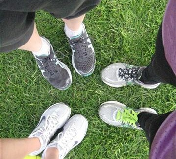 Close up photo of three people's running shoes