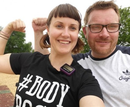 Photo of personal trainer and client smiling after exercise and flexing their muscles