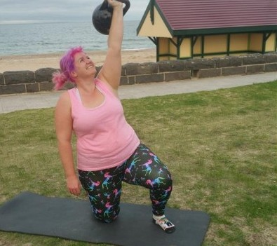 Woman doing kettlebell exercise at the beach