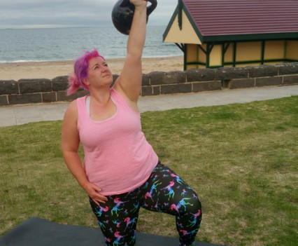 Female doing a kettlebell exercise at the beach