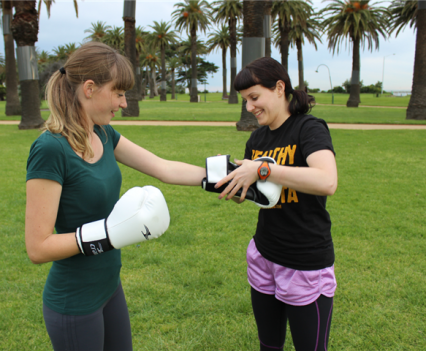 Personal Trainer is putting gloves on a female client outdoors